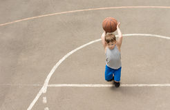 Little boy playing on a basketball court. About to throw the ball which he is holding raised in his hands, view from above Stock Photo