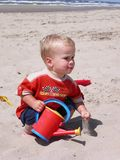 Little boy playing on the beac. Little boy playing with sand on the beach stock image