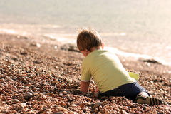 Little boy playing on a beach. Covered in pebbles Royalty Free Stock Images