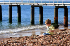 Little boy playing on a beach. Little boy throwing a stone on the beach Stock Image