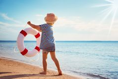 Little boy playing at the beach in hat royalty free stock images