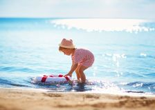 Little boy playing at the beach in hat royalty free stock photography
