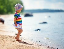 Little boy playing at the beach in hat Stock Images