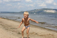 Little boy playing on the beach near the river Royalty Free Stock Photography
