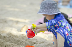 Little Boy playing on the beach. Play sand, with beach toys, with a blue hat Royalty Free Stock Image