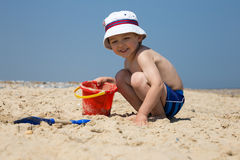 Little boy playing on the beach Stock Images