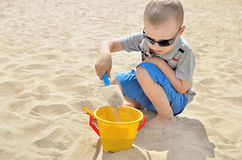 Little boy playing on the beach in the sand. Child sculpts figures out of the sand. Activities in the summer on the sea Royalty Free Stock Image
