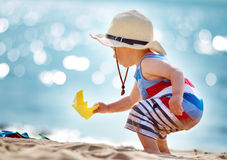 Little boy playing at the beach in straw hat Stock Images