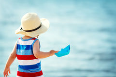 Little boy playing at the beach in straw hat royalty free stock photos