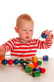 Little boy playing with beads Stock Images