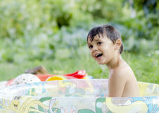 Little boy playing. Beautiful little boy playing with water from the pool on a summer day royalty free stock photo