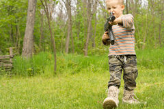 Little boy playing at being a soldier Stock Images