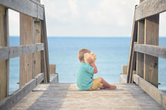 Little boy playing with big seashell near the ocean Stock Image