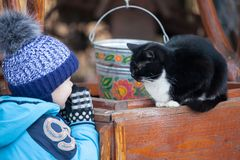 Little boy playing with a black cat. Black and white cat sitting on wooden well outdoors in the back yard stock photos