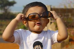 Little boy playing with brown goggle, Palande, Kokan stock photo