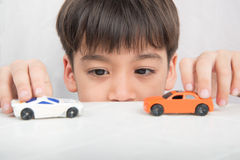 Little boy playing with car toy on  the table alone Royalty Free Stock Photography