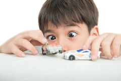 Little boy playing with car toy on  the table alone Stock Images