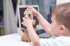 little boy playing with a cardboard robot at home on a white table Stock Photography