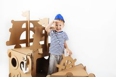 Little boy playing with cardboard ship on white background. Happy kids. Cute child dressed as a sailor. Childhood. Fantasy, imagination royalty free stock images