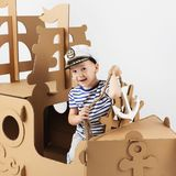 Little boy playing with cardboard ship on white background. Happy kids. Cute child dressed as a sailor. Childhood. Fantasy, imagination stock photo