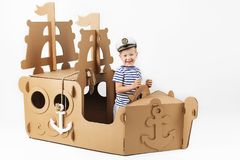 Little boy playing with cardboard ship on white background. Happy kids. Cute child dressed as a sailor. Childhood. stock photography