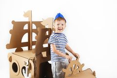 Little boy playing with cardboard ship on white background. Happy kids. Cute child dressed as a sailor. Childhood. Fantasy, imagination stock photos