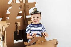 Little boy playing with cardboard ship on white background. Happy kids. Cute child dressed as a sailor. Childhood. Fantasy, imagination royalty free stock photos