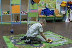 Little boy playing cars on the carpet. Entertainment of childhood. royalty free stock photos