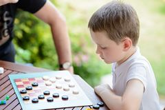 Little boy playing checkers board game. With his grandpa on the terrace stock photography