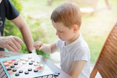 Little boy playing checkers board game. With his grandpa on the terrace royalty free stock photo