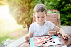 Little boy playing checkers board game. On the terrace stock photography