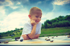 Little boy playing checkers in park Stock Images