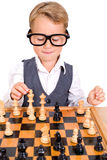 Little boy playing chess Stock Images