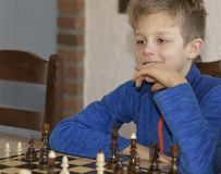 Little boy is playing chess. A little boy is playing chess.thinks which is better to make a move Stock Photography