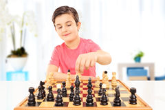 Little boy playing chess seated on a table Stock Image