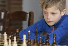 Little boy is playing chess. A little boy is playing chess.thinks which is better to make a move Royalty Free Stock Image