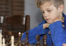 Little boy is playing chess. A little boy is playing chess.thinks which is better to make a move Stock Photo