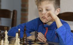 Little boy is playing chess. A little boy is playing chess.thinks which is better to make a move Royalty Free Stock Images