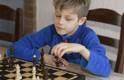 Little boy is playing chess. A little boy is playing chess.thinks which is better to make a move Stock Image