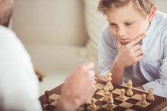 Little boy playing chess together with father at home. Focused little boy playing chess together with father at home Royalty Free Stock Photography
