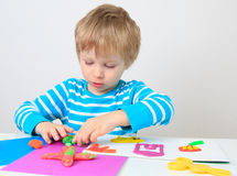 Little boy playing with clay dough stock images