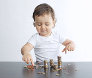 Little boy playing with coins Stock Photos