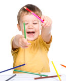 Little boy is playing with color pencils Stock Images