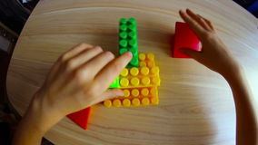 Little boy playing in the colored blocks sitting stock video