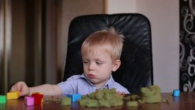 Little boy playing with colored sand at home. stock footage
