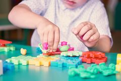 Middle section of little boy playing with colorful plastic bricks at the table. Kids having fun and building out of. Little boy playing with colorful plastic royalty free stock photos