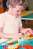 Little boy playing with colorful plastic bricks at the table. Toddler having fun and building out of bright constructor. Bricks. Early learning. Developing toys stock images