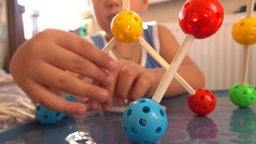 Little boy playing with colorful plastic construction set. Molecule models. 4K close up video. Unrecognizable little boy playing with colorful plastic stock footage