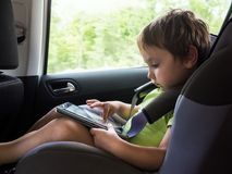 Little boy playing on computer tablet  in the car Stock Images