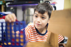 Little boy playing connect four game soft focus at eye contact Stock Photo